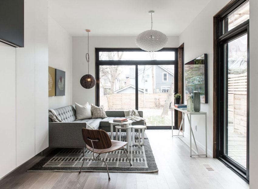 Sala de estar, con muebles de tonos grises y blancos, con lámparas colgantes.