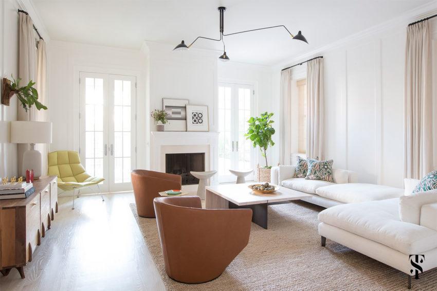 Sala de estar está decorada, con un sofá blanco y sillones de cuero marrón caramelo.