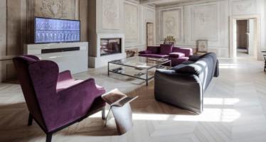 Sala de estar con sofás de colores fuertes, combinado con modernas mesas. Paredes antiguas y decoradas clásicamente