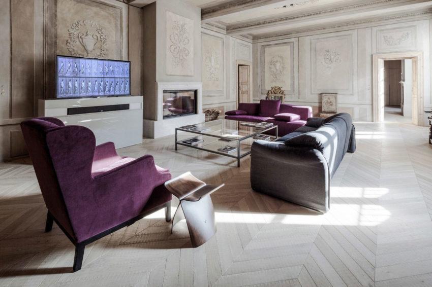 Sala de estar, con sofás de colores fuertes, combinado con modernas mesas. Paredes antiguas y decoradas clásicamente