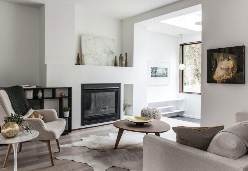 Sala decorada en tonos claros y acogedores, donde destaca la chimenea.