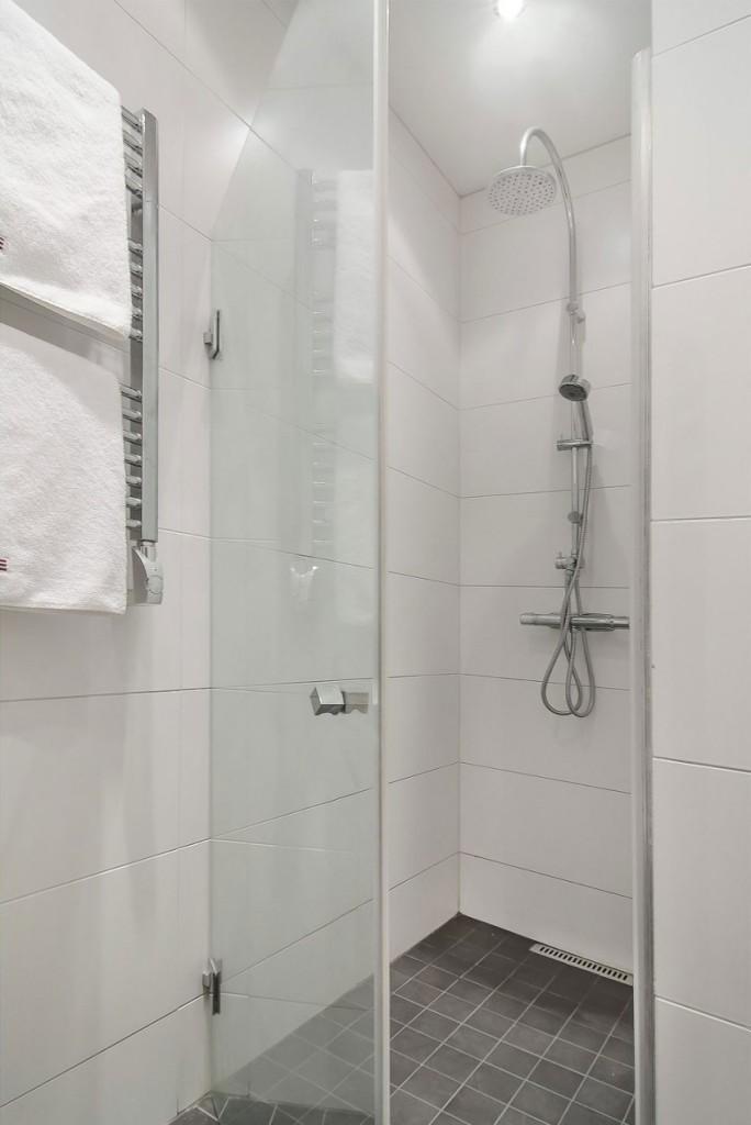 Imagen de la ducha y del toallero radiador, del cuarto de baño.