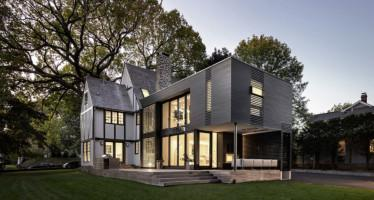 Vista trasera de la casa. Terraza con suelo de madera y muebles de jardín