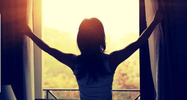 Mujer-abriendo-ventana-cuando-sale-el-sol-alopecia-Areata